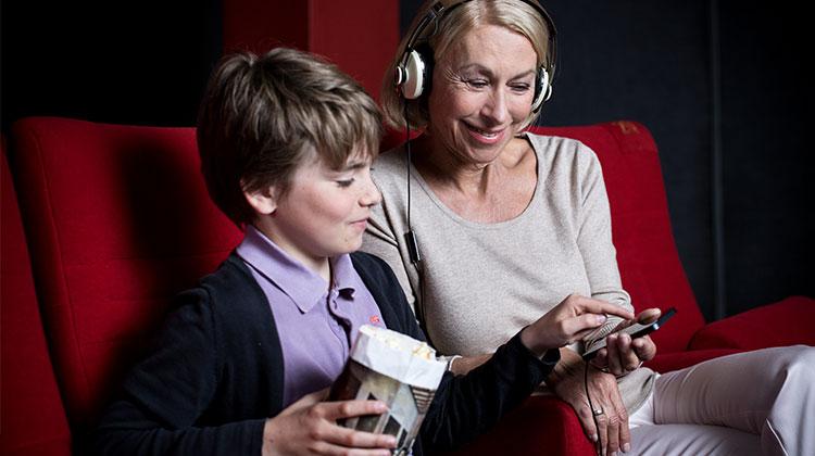 Ein Junge zeigt seiner Großmutter auf dem Smartphone welcher Kanal der App für sie Audiodeskription und welcher Hörunterstützung bietet.
