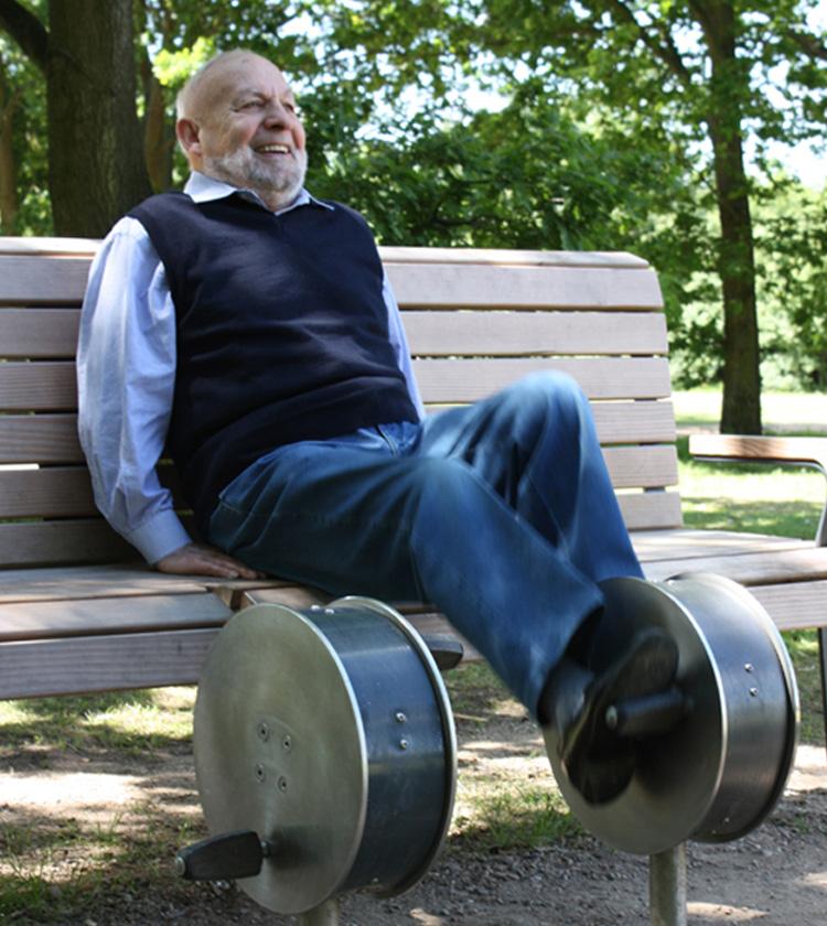 Ein älterer Herr benutzt den Radtrainer, ein Trainingsgerät von Giro Vitale, während er auf der Bank sitzt