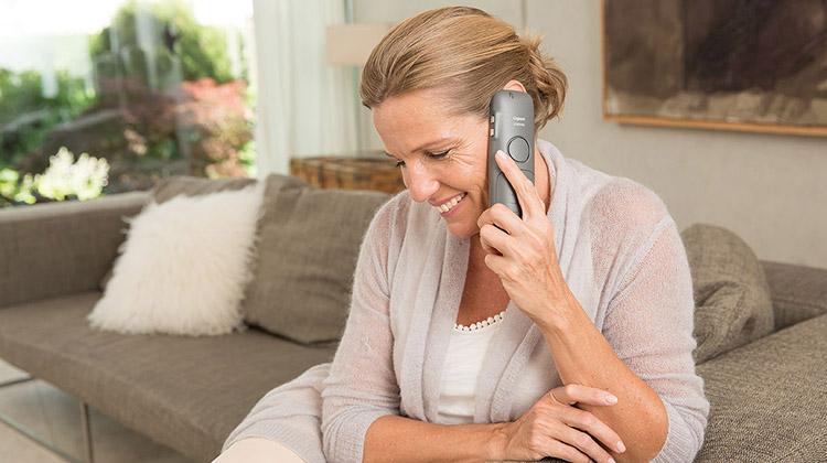Ältere Dame telefoniert mit DECT telefon und gut dabei auf unscharfeFrau sitz auf Sofa mit gesenktem Blick und telefoniert mit DECT-Telefon