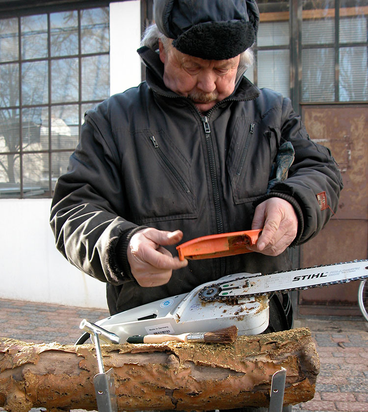 Älterer Herr demontiert eine elektrische Kettensäge. Dabei guckt er konzentriert auf die Säge.
