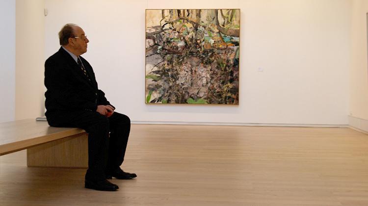 Besucher sitzt auf einer Bank und schaut sich ein Bild der Kunsthalle an.