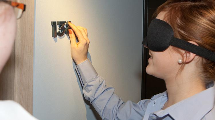 Mitarbeiterin des Scandic-Hotels trägt Maske zum Verdunkeln der Augen und ertastet eine reliefartige Zimmernummer