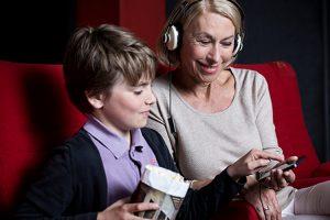 Ein Junge zeigt seiner Großmutter auf dem Smartphone den Kanal für Audiodeskription und Hörunterstützung.
