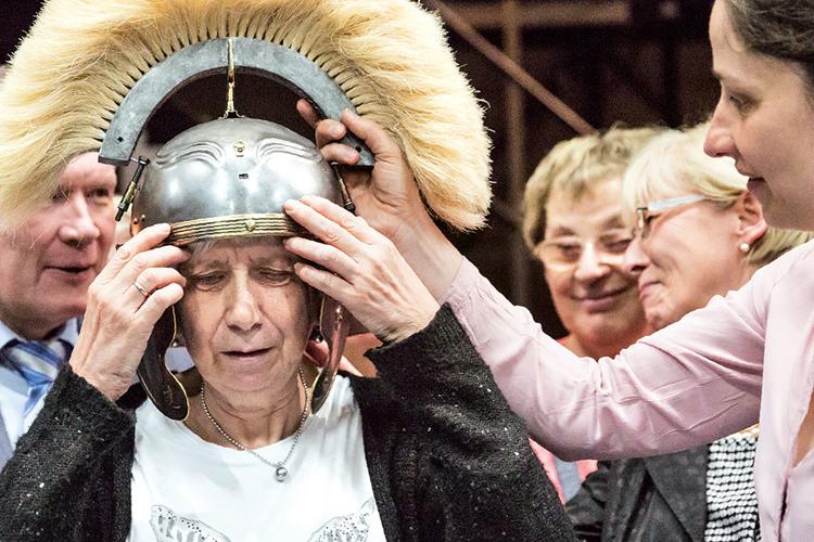 Eine Museumsbesuchern setzt sich einen Helm aus einer Ausstellung auf den Kopf